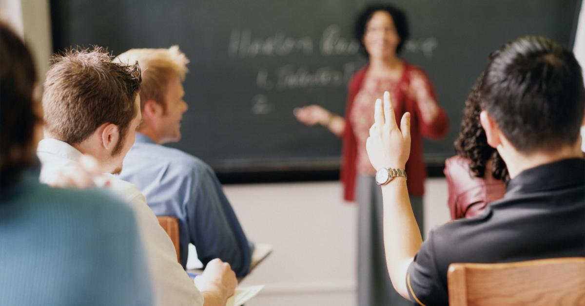 En lärare håller kurs framför vuxna studenter.