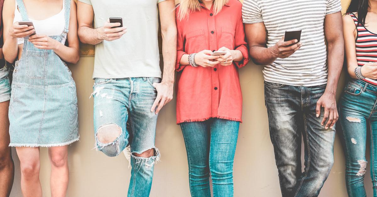 fem personer håller i smarta telefoner och står mot en vägg