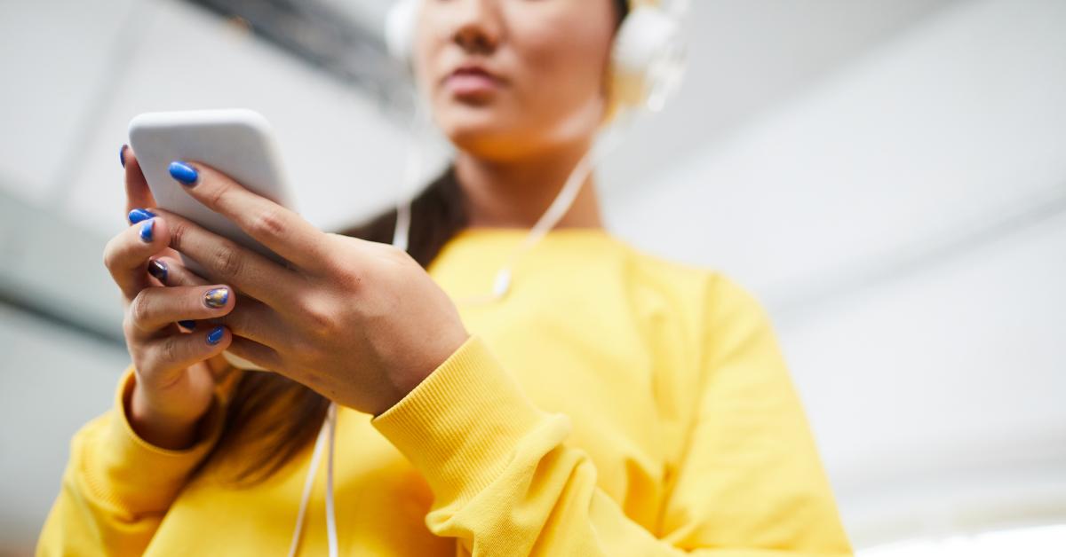 En tjej klädd i gult och med hörlurar scrollar i sin smarta telefon