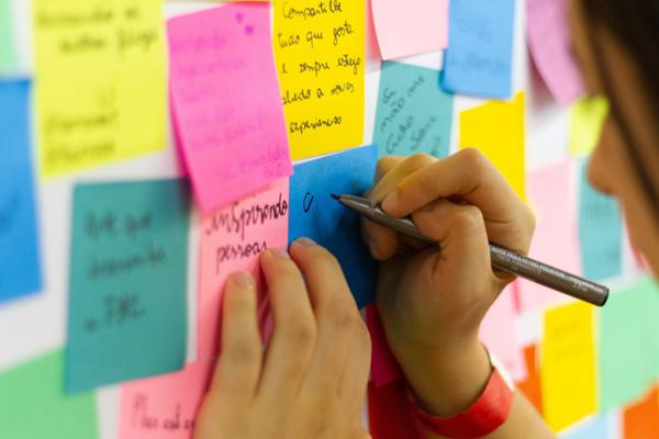 en anslagstavla fylld med post-it-lappar. En person antecknar på en av lapparna. När du jobbar med din sociala medier strategi mall kan du också jobba på det viset, för att visualisera dina mål och målgrupper.