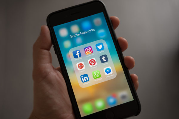 en smart telefon som visar ikoner för sociala medier i någons hand.