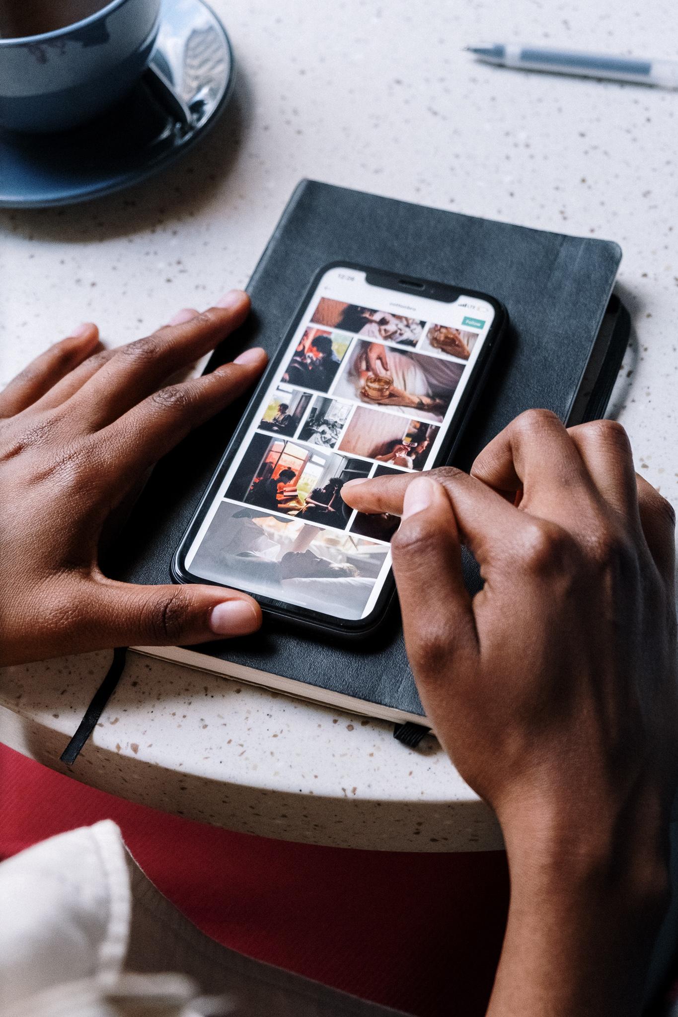 två händer skrollar igenom en smartphone, gör en digital audit eller en översyn av någons sociala medier kanaler
